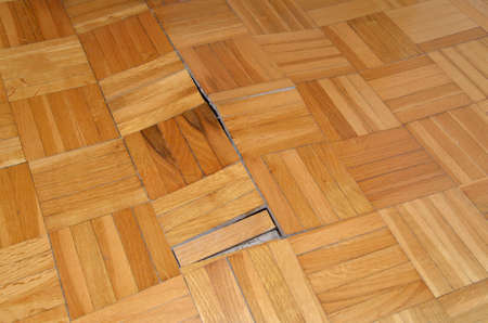 Damaged parquet in a living room of an apartment Фото со стока