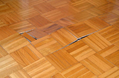 under the influence: Wooden floor starts to lift up under influence of moisture or water. Stock Photo