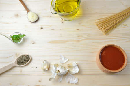 aceite de cocina: Ingredients - pasta, spices, herbs, tomato sauce and olive oil - for preparing spaghetti on wooden table Foto de archivo