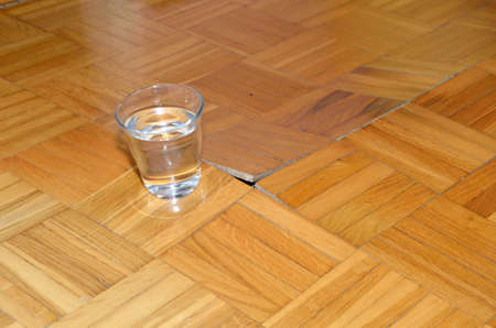 under the influence: Parquet starts to lift up under influence of water. Stock Photo