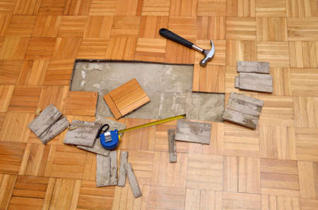 Renovation of damaged wooden floor of apartment, with hammer and measure tape
