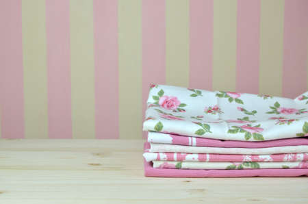 stripped: Pile of pink dishtowels with romantic patterns in front of stripped kitchen wall