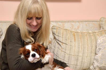 puppy love: la mujer de relax, mimos y besar a su mascota sonriendo, Cavalier King Charles Spaniel (Blenheim)