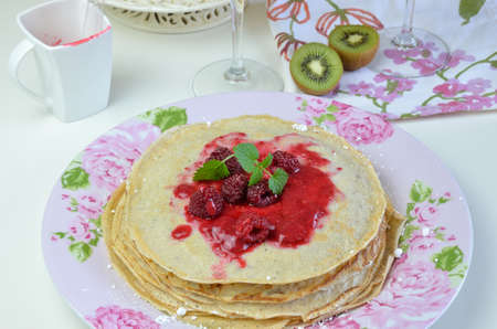 raspberry jelly: Pile of soft pancakes with natural raspberry jelly and lemon balm on top on floral plate Stock Photo