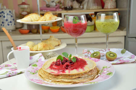 raspberry jelly: Soft pancakes with natural raspberry jelly with just made raspberry and kiwi smoothies served for breakfast Stock Photo