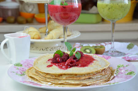 raspberry jelly: Soft pancakes with fresh raspberry jelly with just made raspberry and kiwi smoothies served for breakfast Stock Photo