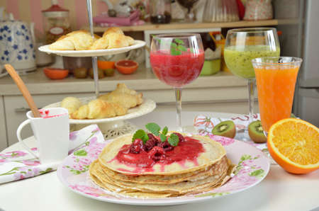 raspberry jelly: Pile of soft pancakes with natural raspberry jelly with just made smoothies of raspberry and kiwi served for breakfast