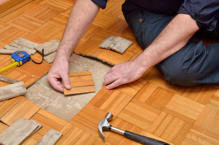 wood flooring: Worker repairing parquet in apartment damaged by moisture or water