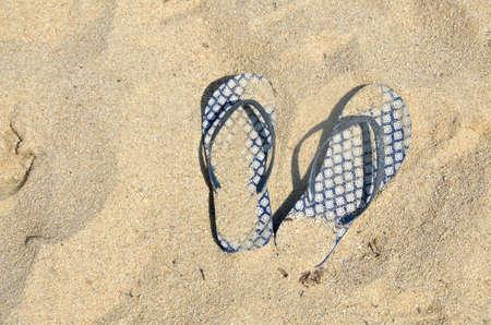 flipflops: Blue flip flops covered with sand left on beach