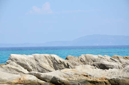 rocks water: Sea rocks and turquoise sea water with land in distance
