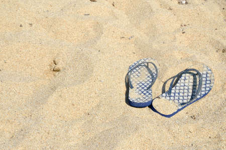 flops: Blue flip flops on golden sandy beach