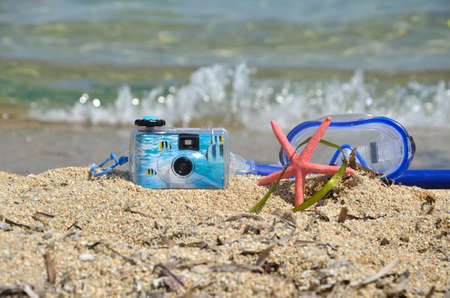 masque: Water camera, snorkeling masque and sea star on sandy beach Stock Photo