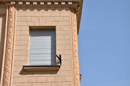 renovated: Window covered with sunblind on a renovated building facade and blue sky