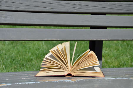 school yard: Open book on a bench in the school yard on a windy day