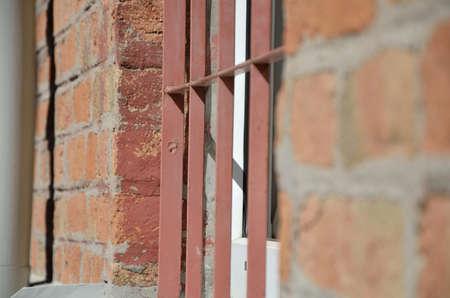 rejas de hierro: Ventana en pared de ladrillo protegida con barras de hierro Foto de archivo