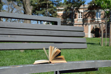 Open book on bench in the school yard on a windy day Stock Photo