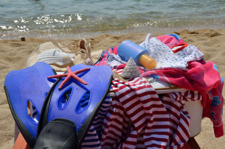 unpacked: Summer clothes unpacked from suitcase on the beach