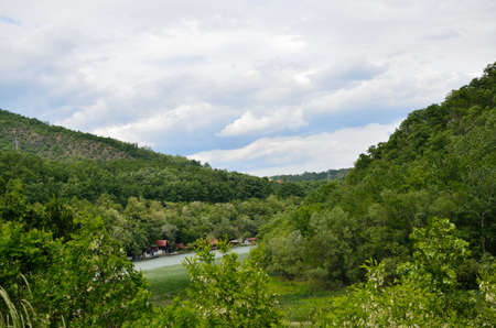 lodges: Hills,valleys and river with river lodges under spring sky Stock Photo
