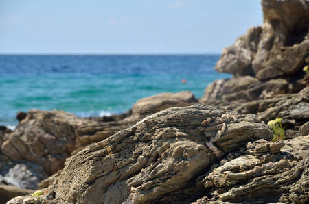 Rocks and turquoise sea water in background in summer time