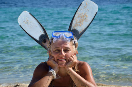 masque: Woman with diving masque and flippers on beach with sea in background