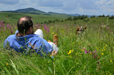 Man lying on a spring meadow and looking after his dog Stock Photo
