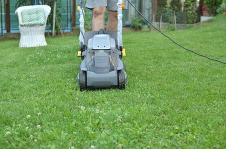 cut grass: Man is pushing a mower to cut grass in his garden Stock Photo