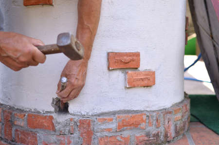 making hole: Making a hole in a concrete by hands with hammer and chisel Stock Photo