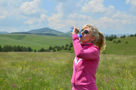 Woman dressed in sport clothes drinking water from a plastic bottle in a picturesque landscape. Stock Photo