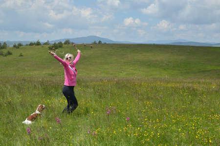 Femme avec un chien danse dans un champ à jour de printemps et d'écouter la musique de son téléphone mobile sur le casque