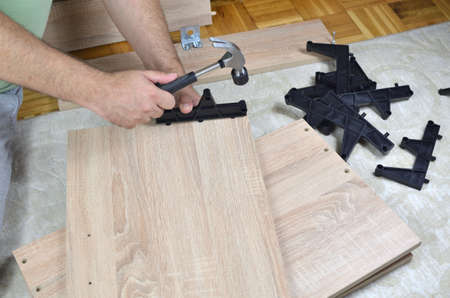 hammering: Hammering plastic parts on a drawer of a shoe cabinet