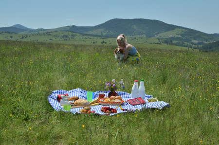 Mujer sosteniendo a su perro en sus brazos en picnic en la naturaleza Foto de archivo