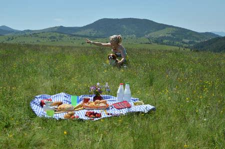 Mujer mostrando algo a su perro en la distancia en el exuberante picnic en el paisaje Foto de archivo