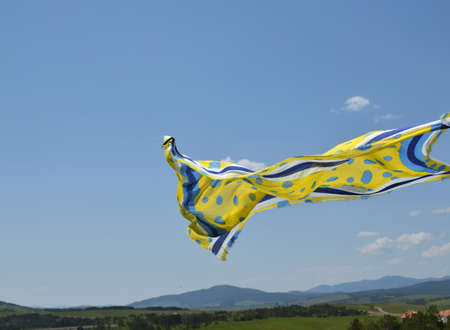 Yellow and blue scarf waving in wind with blue sky and hills behind