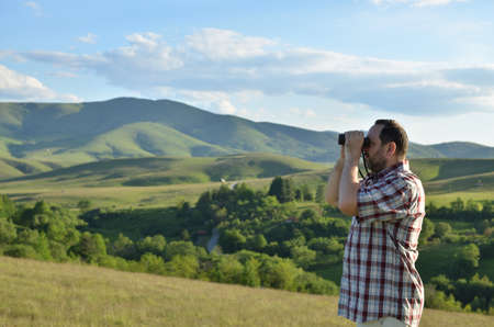 birdwatcher: Man is using binoculars to explore wonderful summer scenic landscape in mountain