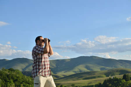 birdwatcher: Man is using binoculars to watch divine summer scenery of green forest and grass on surrounding hills and mountain