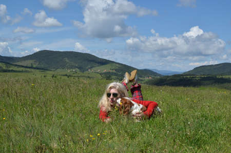 Woman dressed in red lying with her dog (Cavalier King Charles Spaniel) on a mountain meadow and divine landscape in background