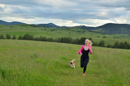 Lady in pink and black sportswear jogging with her dog in landscape on a cloudy day Stock Photo