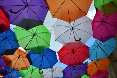 opened: Opened colorful umbrellas with a part of cloudy sky Stock Photo