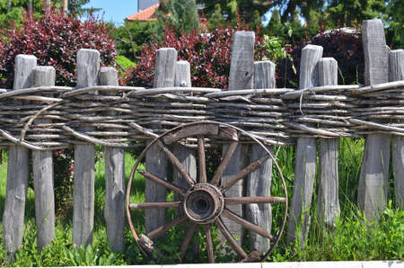 old wood farm wagon: Old wheel of a traditional cart leaning on a wooden fence