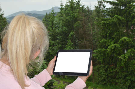 ponytail: Blonde woman with ponytail looking at landscape and her tablet white screen suitable for copy text or picture Stock Photo
