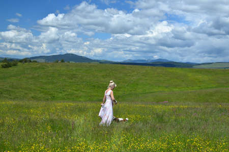 Woman walking with her pet dog in a mountain meadow on Zlatibor Mountain