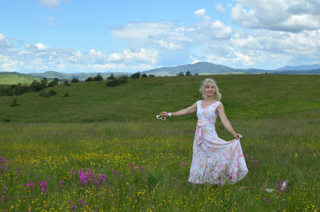 Woman in romantic walk in a meadow with her dog (dog is hardly visible because of high grass)
