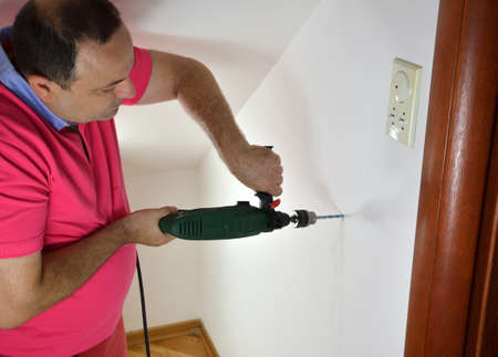 Man drilling a wall at home with a drill