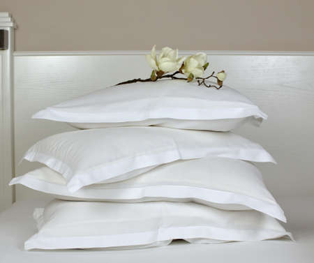 bedhead: Pile of comfortable pillows in white linen on a bedhead with artificial orchid decoration Stock Photo