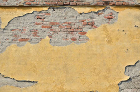 dilapidated wall: Damaged brick wall with yellow colored molter as a background