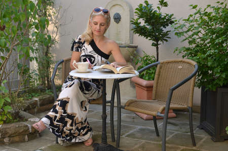 write a letter: Blond woman in an elegant summer dress sitting at a garden table and writing in her notepad