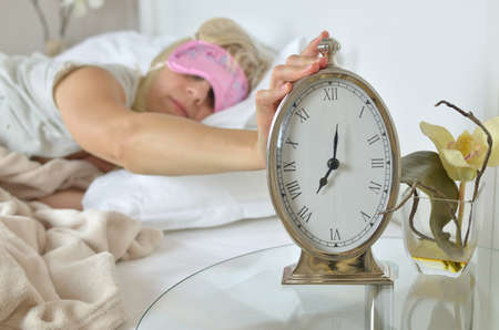 Silver clock showing seven oclock in the morning with a hand of a awake woman on it