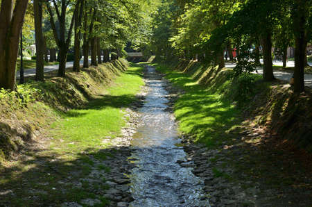 Small river surrounded with lush park trees and with a small bridge in distance