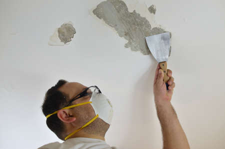 plasterer: Man peeling ceiling with plaster spatula, preparing to handle