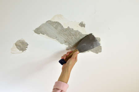 redecorate: Hand holding a plaster spatula, scraping a ceiling, preparing it for renovation